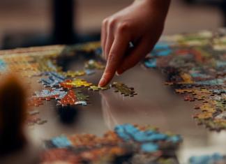 mano haciendo puzzle sobre mesa de cristal